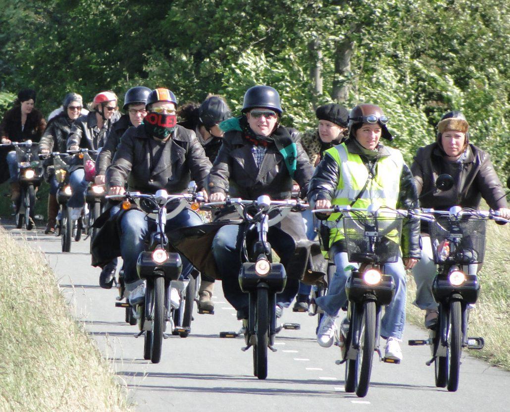 Mensen op een solex zijn op een fietspad in een bosrijke omgeving aan het solex rijden.