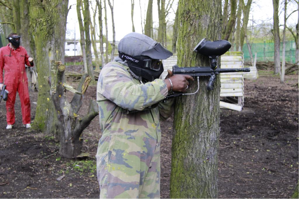 Man staat verstopt achter en boom tijdens paintballen